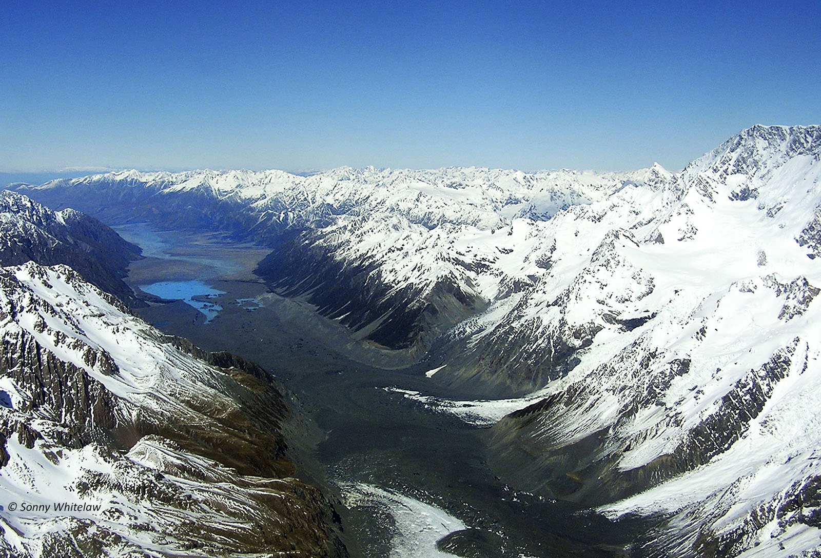 Tasman Glacier (foreground – darker areas are moraine over the ice) on the eastern side of Aoraki Mt Cook (right), and Tasman River (centre back)